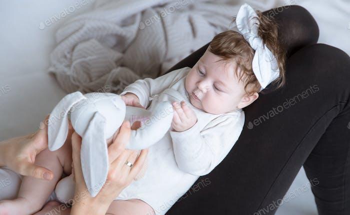 Мама играет с игрушкой с новорожденной дочерью.