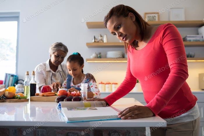 Mother looking recipe book while grandmother and granddaughter chopping vegetables