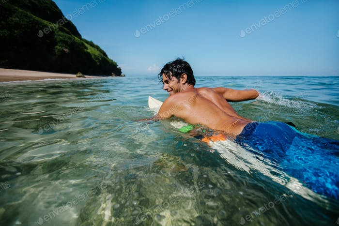 Male surfer in the ocean water with surf board