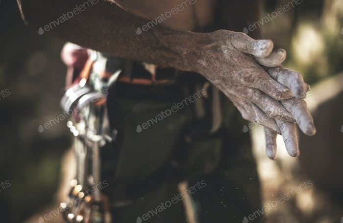 Nahaufnahme eines Kletterers, der weißes Kreidepulver über seine Hände ausbreitet.
