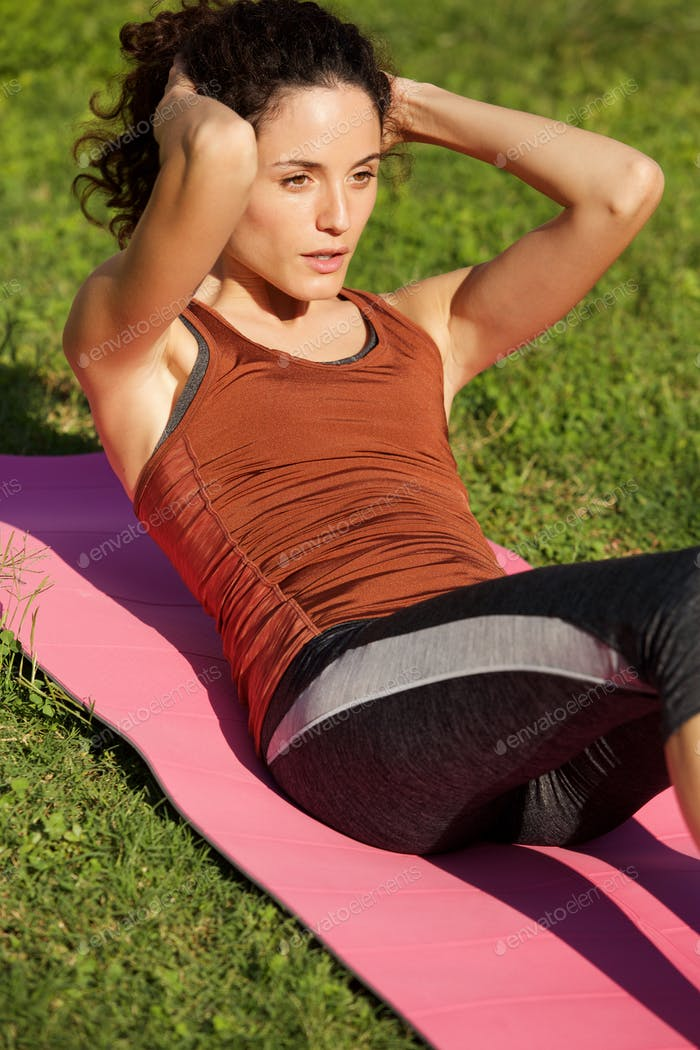 healthy young woman doing sit up exercise outside