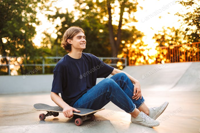 Young smiling skater in black T-shirt and jeans happily spending