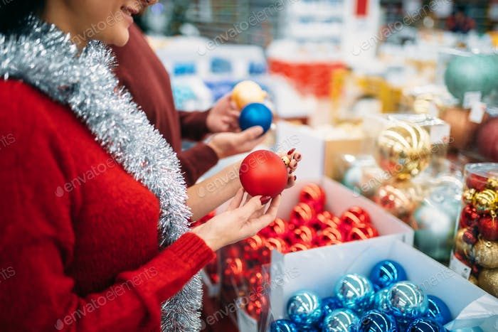 Female person buying christmas tree balls