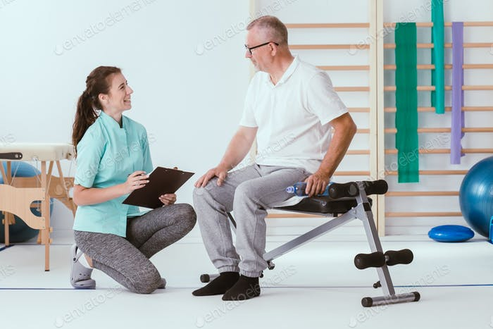 Injured older man and a young professional physiotherapist prepare for gym exercises