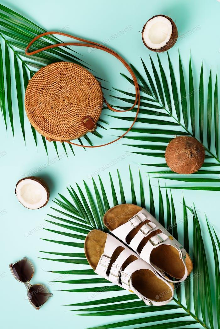 Stylish rattan bag, coconut, birkenstocks, palm branches, sunglasses on blue background. Banner. Top