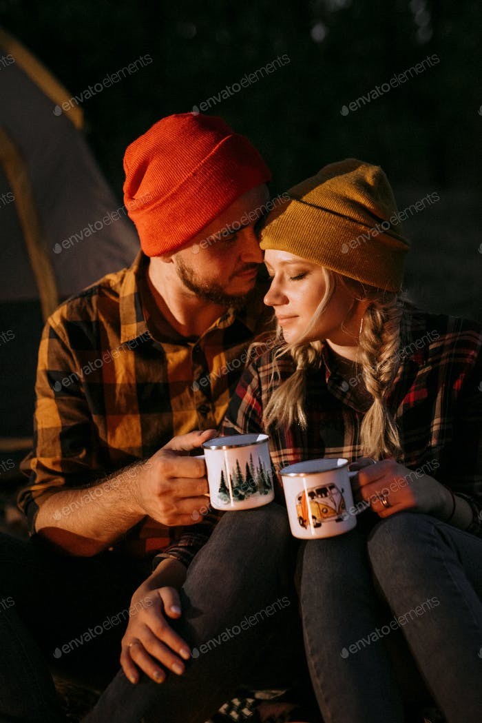 Young couple a guy and a girl in bright knitted hats stopped at a camping