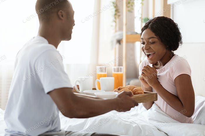 Romantic black husband bringing breakfast in bed for his wife
