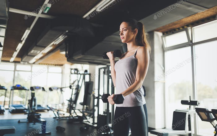 Sporty strong woman working out in gym