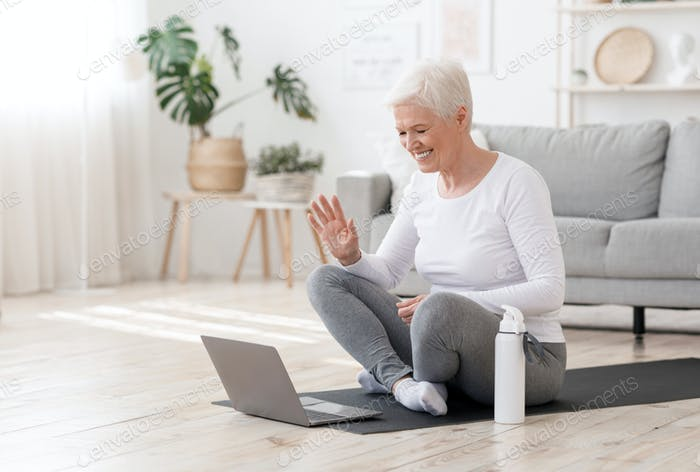 Smiling Senior Woman Training At Home Online Via Laptop, Waving At Camera