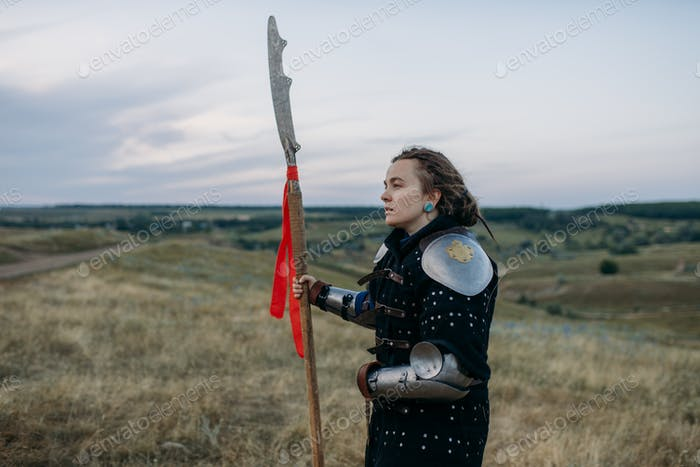 Female medieval knight with spear poses in armor