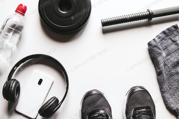 Toalla, zapatillas y smartphone con auriculares sobre fondo blanco