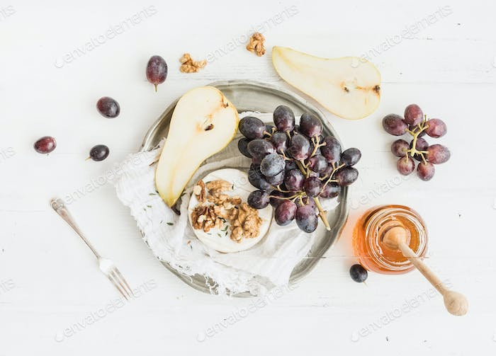 Camembert cheese with grape, walnuts, pear and honey on vintage metal plate