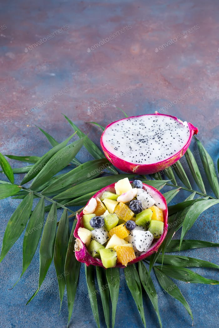 Exotic fruit salad served in half a dragon fruit on palm leaves on stone background, copy space