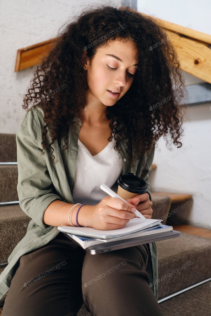 Student girl sitting on stairs with cup of coffee to go and thoughtfully writing in notebook