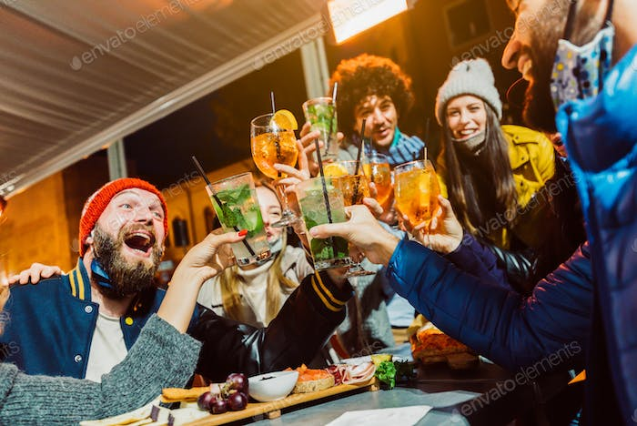 Group of friends drinking at cocktail bar with open face masks