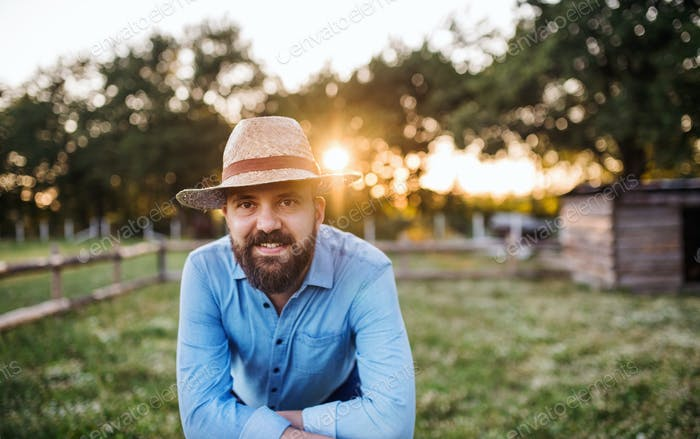 Ein Porträt von reifen Mann Bauer stehend im Freien auf Familienfarm bei Sonnenuntergang