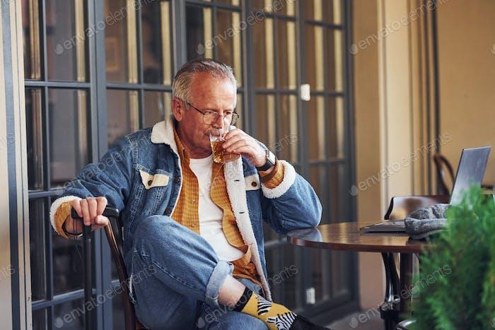 Stilvolle Senior in modischer Kleidung und in Gläsern sitzt im Café mit Getränk