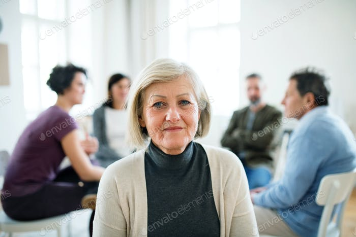 A portrait of senior depressed woman during group therapy.
