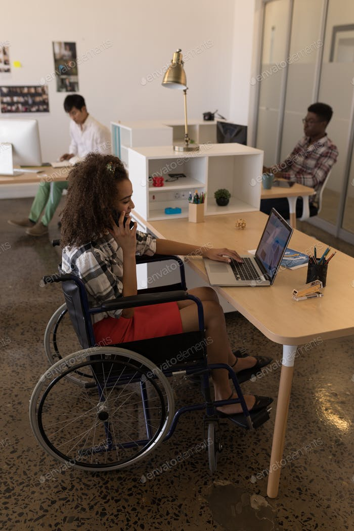 Young disabled mixed-race female executive using laptop while talking on mobile phone