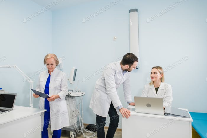 Photo of three doctors together discussing new way of treatment while having a meeting at office