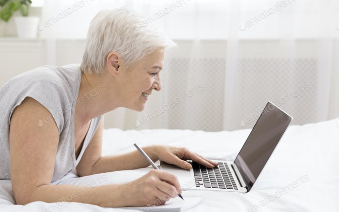 Cheerful skilled senior woman lying in bed