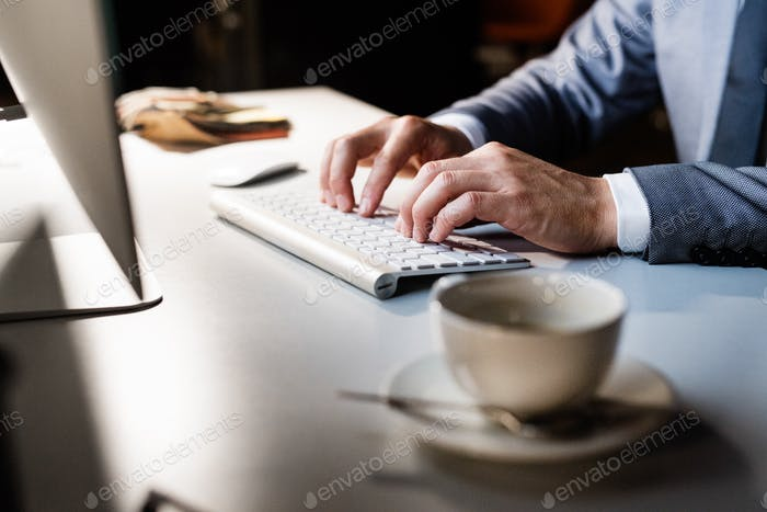Hands on keyboard. Businessman in his office at night.