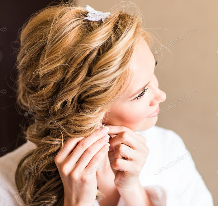 Elegant blonde bride putting on earrings closeup, preparing for wedding