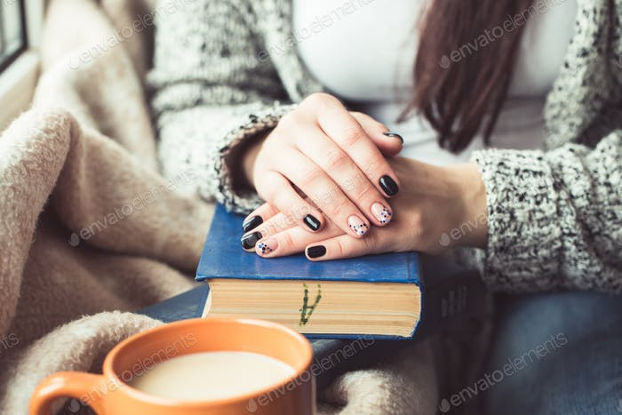 Young woman reading book, close-up, on home interior