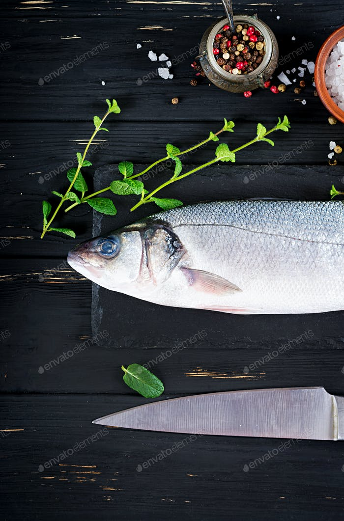 Raw fish. Sea bass on slate blackboard. Ingredients for cooking, grill, baked. Copy space. Top view