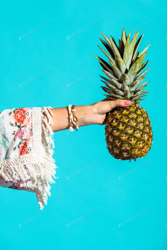 Cropped image of bohemian girl holding pineapple in hand isolated on turquoise