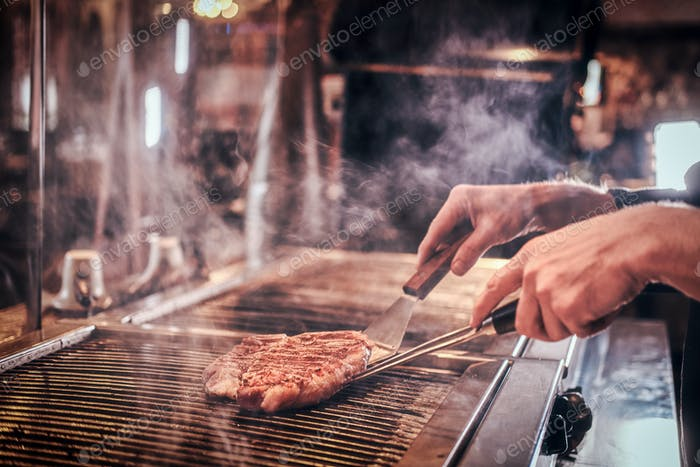 Meisterkoch trägt einheitliche Kochen leckeres Rindfleischsteak in einer Küche in einem Restaurant