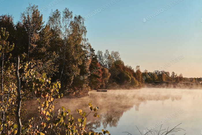Beautiful foggy lake with autumn forest