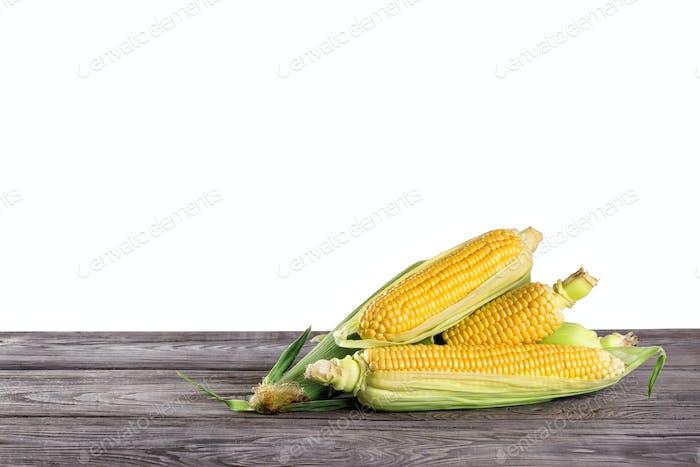 Mais auf Holztisch isoliert auf weißem Hintergrund