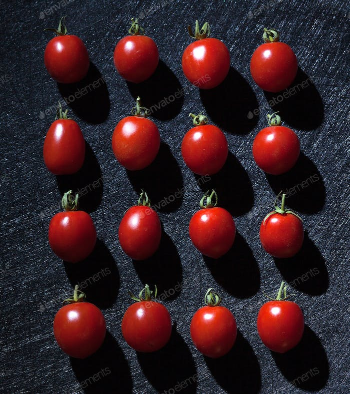 Cherry tomatoes on black background arranged in a linear way.