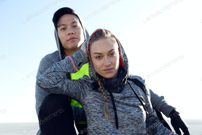 Fit and sporty young couple relaxing after work out in the city.