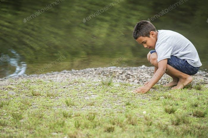 Chico jugando junto a un lago.