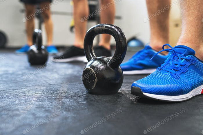 A close-up of legs of three men in gym standing by kettlebells.