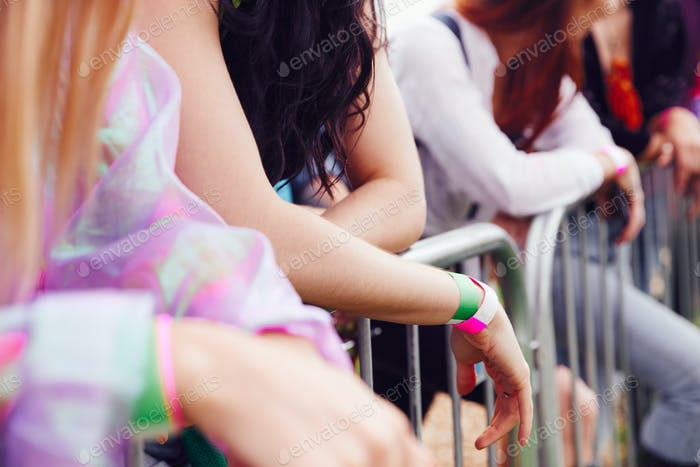 Close Up Of Young Friends Waiting Behind Barrier At Entrance To Music Festival Site