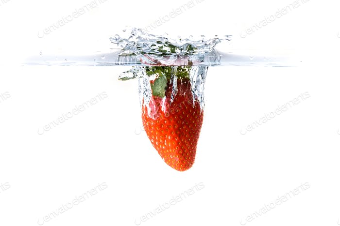 Strawberry splashing into crystal water