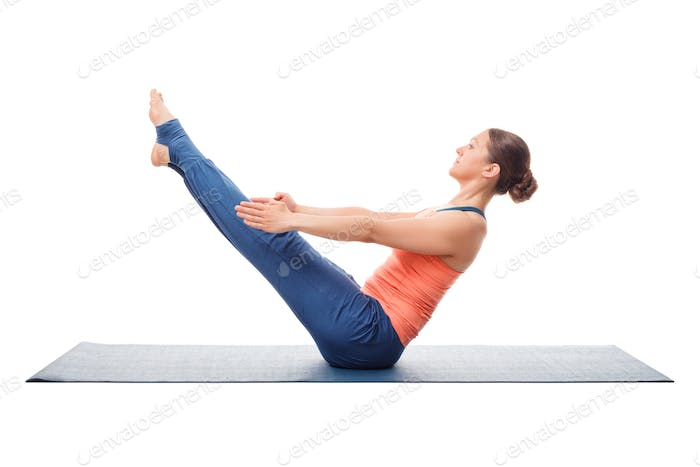 Woman practices yoga asana Paripurna navasana