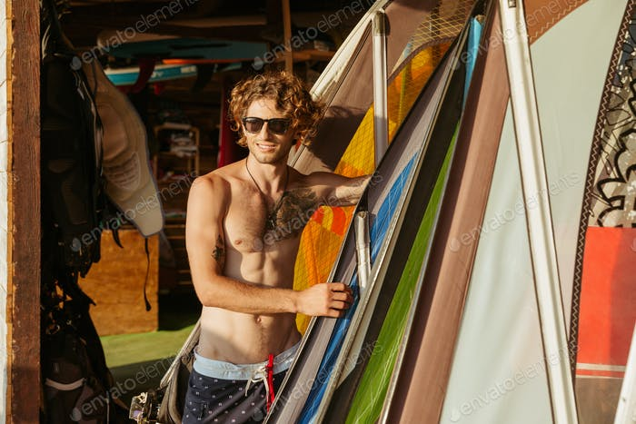 Professional young surfer getting surf board ready to catch waves