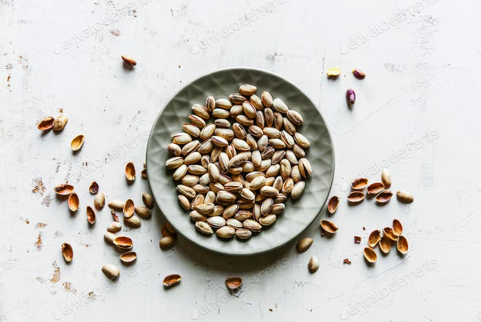 Salted pistachios on a gray plate