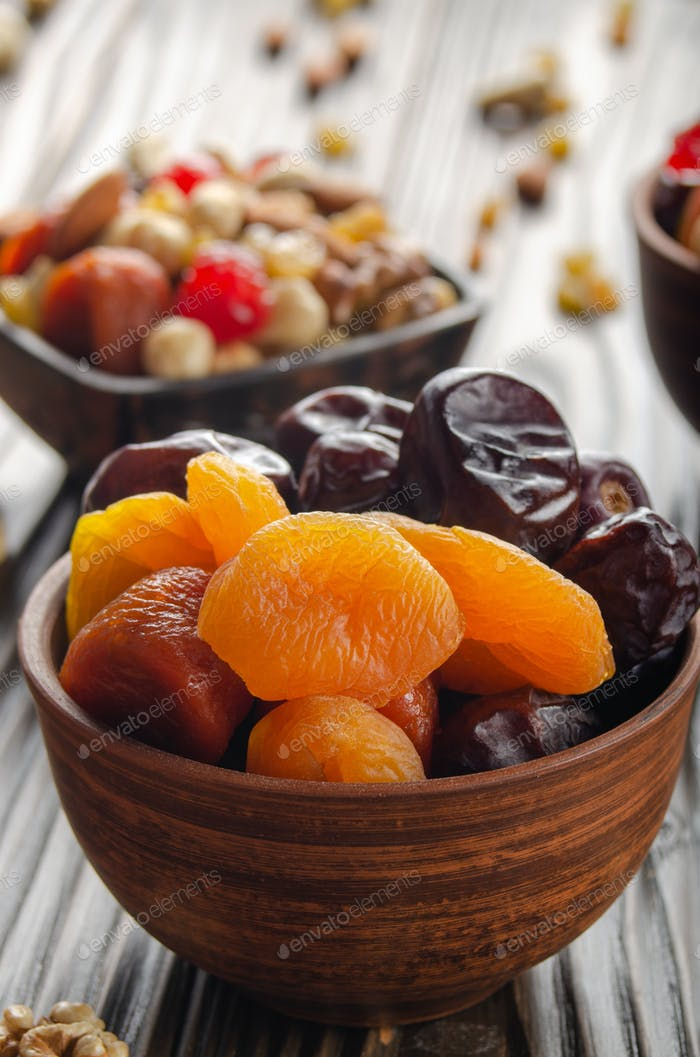 Dried dates and apricots in clay bowl on wooden kitchen table closeup