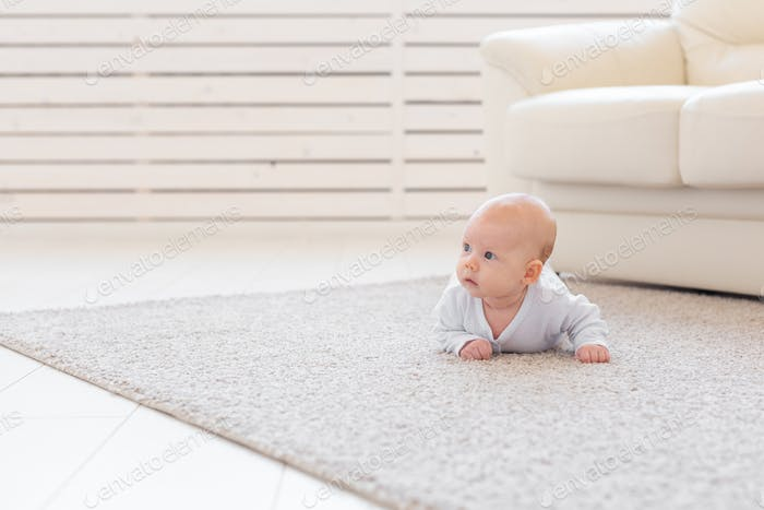 Child, childhood and infant concept - Pretty baby lie on the floor