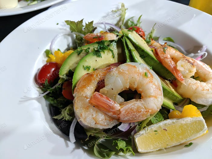Garnelen oder Garnelen und Avocado serviert mit frischem Gartensalat und Zitrone auf weißem Teller