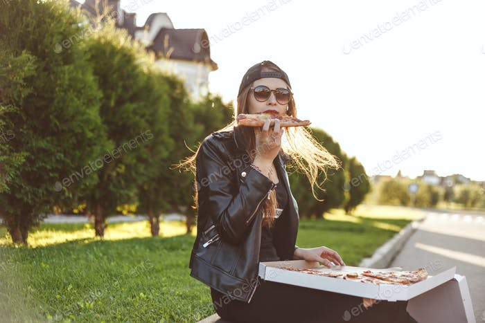 Cheerful young woman enjoying slice of pizza while sitting on curb outdoor