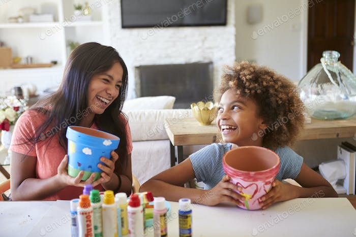 Happy girl and her girlfriend holding plant pots that they've decorated, laughing