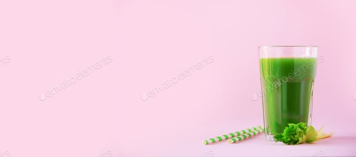 Glass of green celery smoothie on pink background. Banner with copy space. Fresh juice for detox