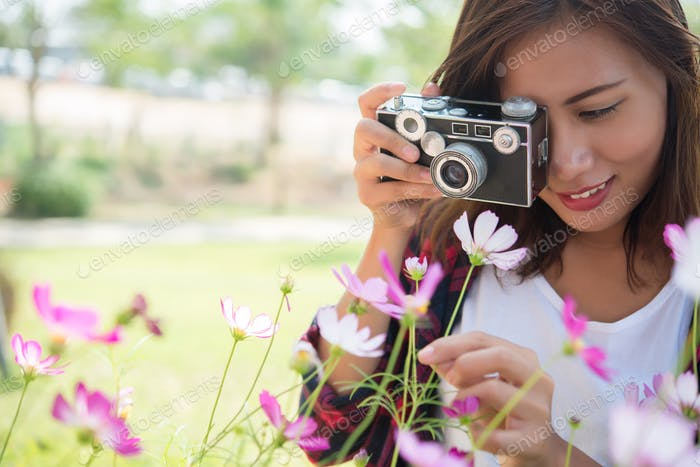 Hipster girl with vintage camera focus shooting flowers at garden.