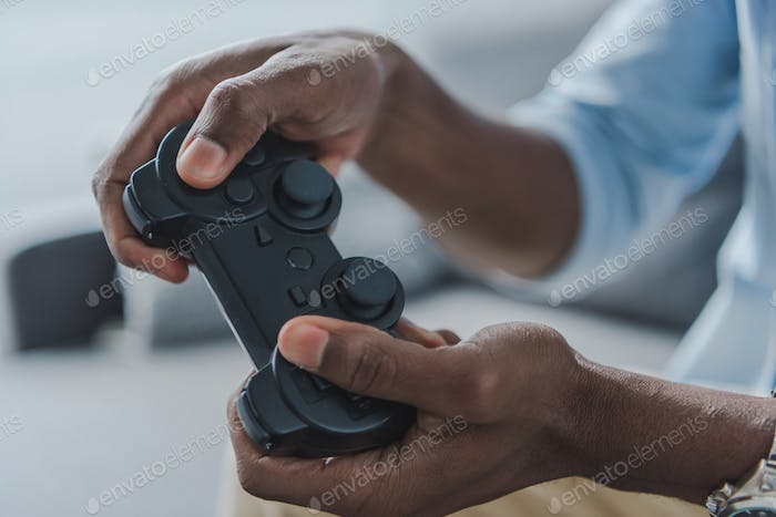 Cropped image of african american man playing video game with joystick at home